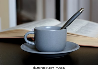 coffee cup with spoon and book aside