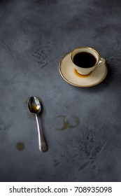 A coffee cup with a spoon on a concrete background