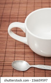 Coffee cup and spoon on a wood background
