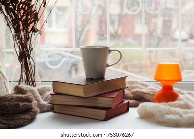 Coffee cup, stack of books, lantern and warm scarf on window siil with bokeh. Reading and rest concept.