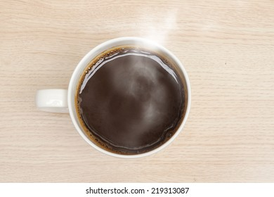 coffee cup with stream on wooden background