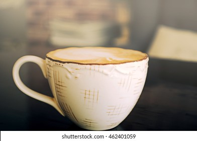Coffee in cup with sunlight on wooden table.