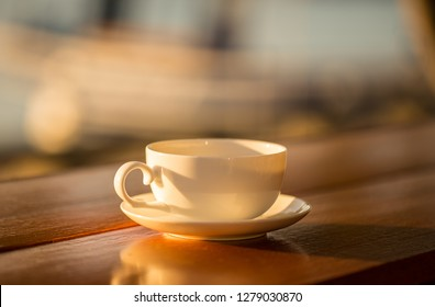 coffee cup with sunset background on wood table.