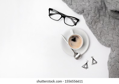 Coffee cup, sweater, lipsticks and glasses. Autumn or Winter feminine concept. Flat lay, top view