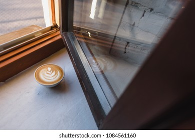 Coffee cup top view on a white rough plaster windowsill