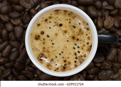 Coffee in a cup top view on roasted cofee beans background, close-up