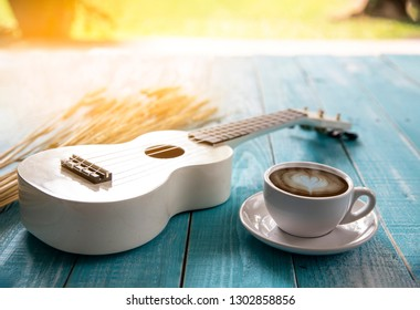coffee cup , a ukulele ,flower on wooden floor background, music instrumentation concept. Decorative in Coffee shop.  -