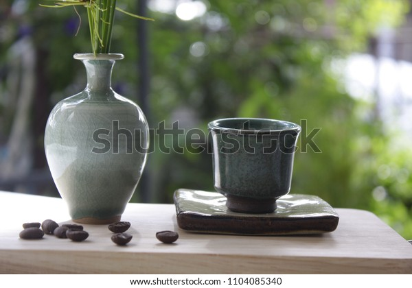 Coffee cup and vintage vase are placed on a wooden shelf.