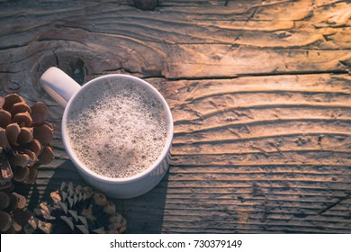 Coffee cup.  White mug of hot drink on rustic wooden table. Romantic, warm morning sunlight, Fall color theme and pine cone. Top view with copy space.