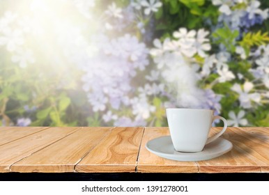 Coffee cup white  placed on wooden table with smoke, With sunrise in garden flower background, With a refreshing concept in the early morning