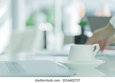 A coffee cup with white plate on the office desk.