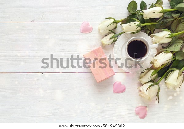 Coffee cup, white rose flowers and gift box on white wooden background. Festive breakfast. Top view, copy space.