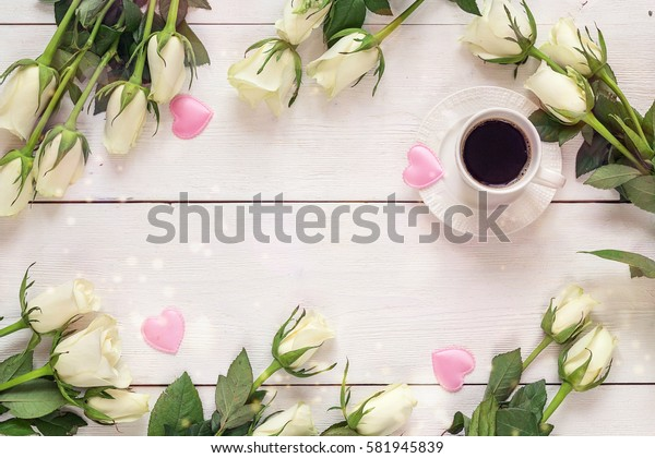 Coffee cup and white rose flowers on white table background. Breakfast on Mothers day or Women day. Top view, copy space.