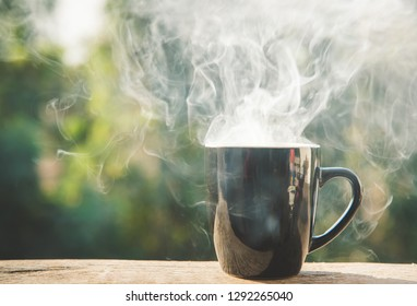 coffee cup with white smoke on blur background.