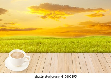 Coffee cup with wood texture on Sugarcane field with sky sunset for background