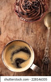 coffee and cupcake in rustic style on wooden table