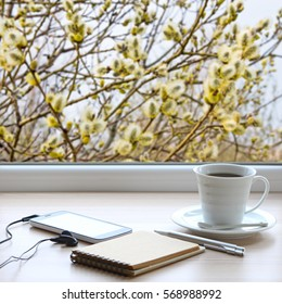 Coffee cup,notebook,pen,smartphone and headphones on a windowsill. Outside, blooming pussy-willow