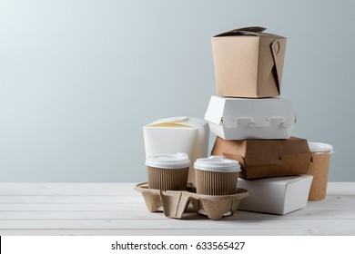 Coffee cups, microwaveable paper take-out food containers, pizza boxes, close-up. Grey background, wooden surface. Eating habits.