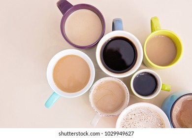 A lot of coffee cups on the beige background. Espresso cup, cappuccino and coffee with milk on the table. Mugs with hot caffeinated drinks. Good morning concept