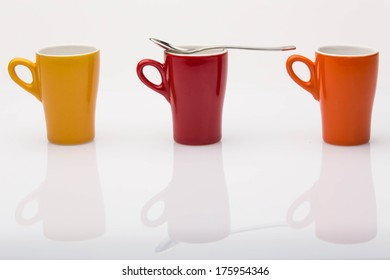 coffee cups on white reflective backdrop