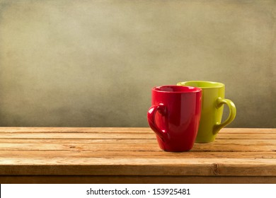 Coffee cups on wooden table over grunge background