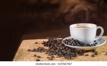 Coffee cups with smoke and coffee beans on the table with dark background
