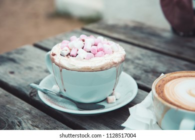 A coffee and decadent and luxurious hot chocolate in a cup and saucer with marshmallows and cream at an outdoor cafe