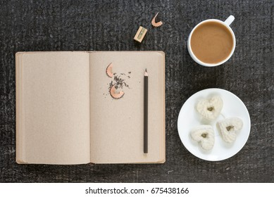 Coffee, diary, pencil and heart-shaped cookies