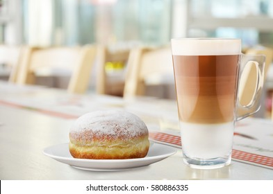 Coffee with donut on white table in restaurant.