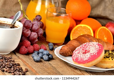 Coffee, donuts, croissant, fresh fruit - grapes, orange and juice in background