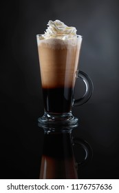 Coffee drink or cocktail with cream on a black background. Copy space for your text.
