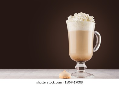 Coffee drink with cream and foam for breakfast in transparent glass with handle in dark brown interior on white wood table, copy space.