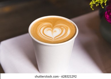 Coffee drink with heart design in cream. Cappuccino or latte with cream.