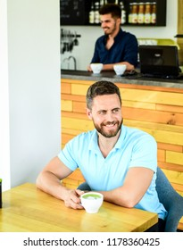 Coffee drinkers live longer. Man bearded guy drinks cappuccino wooden table cafe. Cafe visitor happy smiling face enjoy coffee drink. Improve overall health. Take moment to care about yourself.