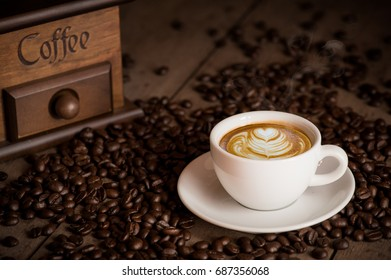 Coffee espresso background, with copy space. Latte art cup of hot coffee, ground coffee, bowl of roasted coffee beans on dark wooden background
