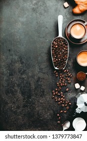 Coffee espresso in dark cups, coffee beant, ground coffee, brown sugar, milk, croissants, capsules.