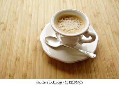 Coffee espresso in a fancy cup, wooden table silver teaspoon