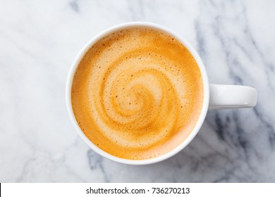 Coffee, espresso in white cup of marble table background. Top view.
