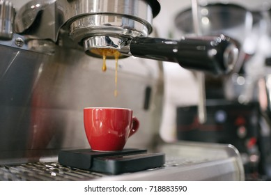 Coffee extraction on espresso machine in the red cup (Selective focus)