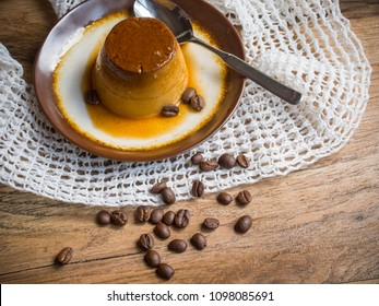 Coffee flan in a plate on wood background