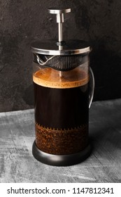 Coffee in french press on dark background