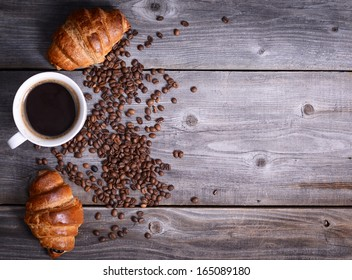 Coffee and fresh croissant on wooden background