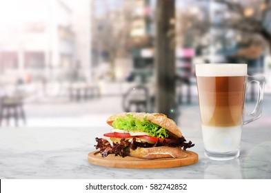 Coffee with fresh sandwich in restaurant.