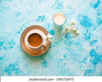 Coffee and a glass of milk on a turquoise background. Ramadan food. Toning.