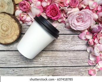 Coffee to go with flowers on wooden background. Take away cup with shabby flowers on pink background.