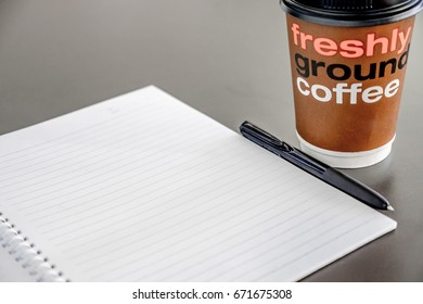 Coffee to go and paper with pen on a table