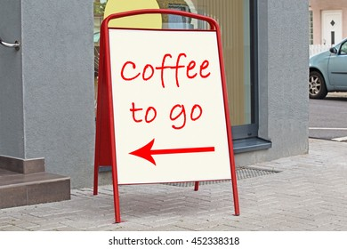 Coffee to go red text and arrow sign on white pointer on  billboard near the entrance on german city street