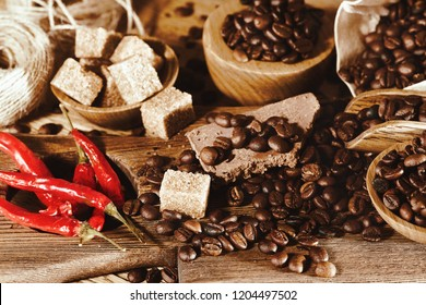 Coffee grain, spices, pepper, chocolate bar and sugar on the table.