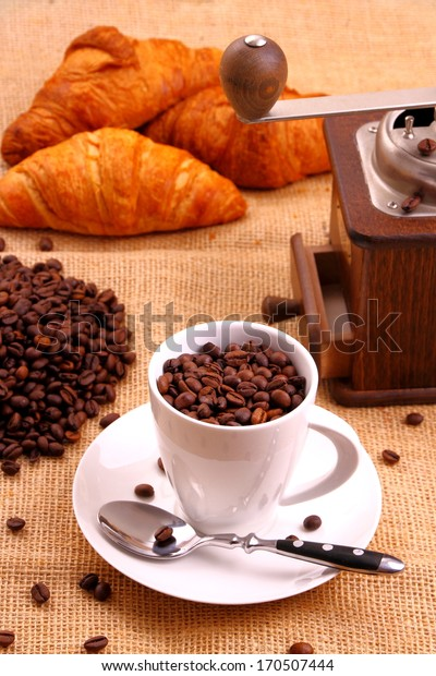 Coffee grain in white cup and croissant, vertical