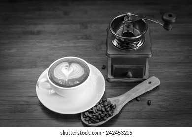 Coffee grinder, cup of coffee on brown wooden background, black and white version